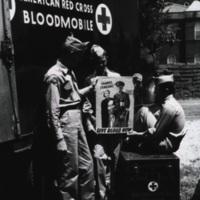 Three servicemen next to an American Red Cross Bloodmobile
